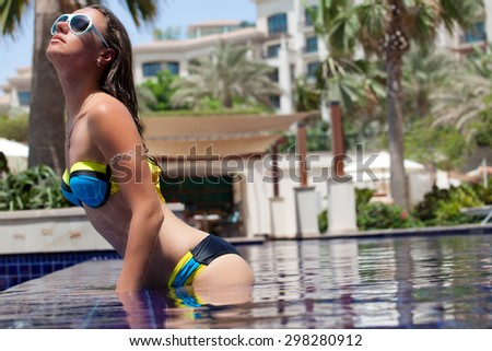 Beautiful woman in the pool at a holiday resort. Happy young female enjoying in the luxury swimming pool. - stock photo