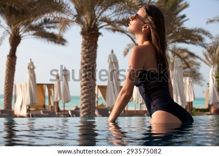 Beautiful woman in the pool at a holiday resort. Portrait of happy young female enjoying in the swimming pool. - stock photo
