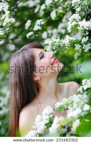 beautiful woman in the spring, in the lush garden. - stock photo