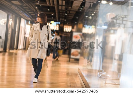 Beautiful woman in trench coat window shopping in department store