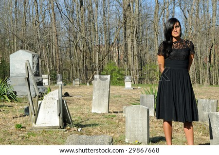 Beautiful woman in vintage dress standing in grave yards - stock photo