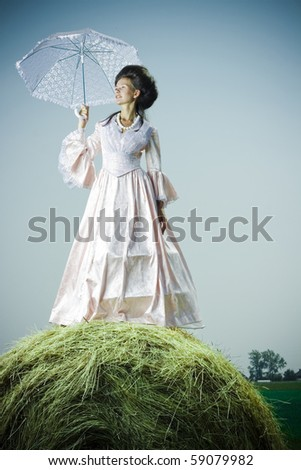 Beautiful woman in vintage dress standing on haystack - stock photo