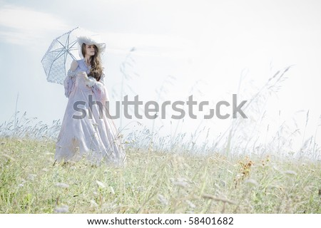 Beautiful woman in vintage dress walking across a field - stock photo