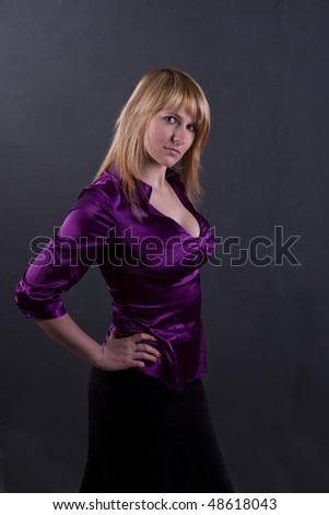 Beautiful woman in violet blouse. A young and attractive female standing on grey background - stock photo