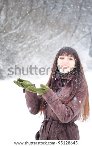 Beautiful woman in warm clothing with snow, catching snowflakes - stock photo