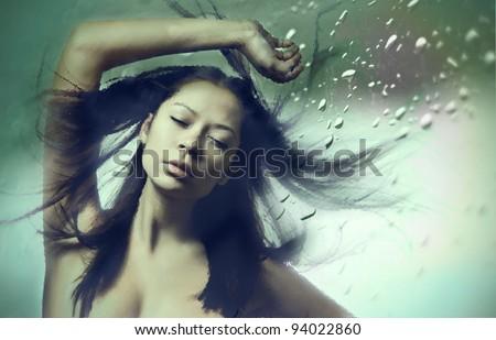 Beautiful woman in water studio - stock photo