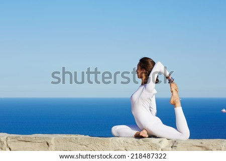 Beautiful woman in white clothes seated in yoga pose on blue sea background, healthy young woman meditating yoga enjoying amazing view of sea from high, practicing yoga at sunny day - stock photo