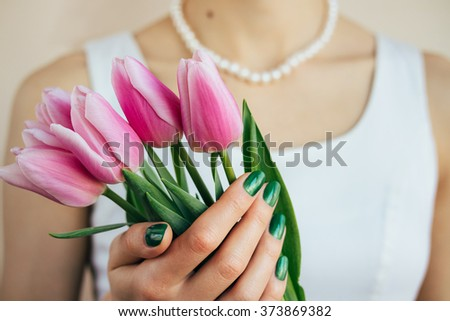 Beautiful woman in white dress and pearl necklace holding a pink tulips, close-up - stock photo