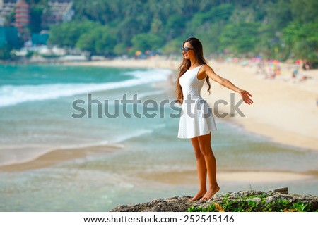Beautiful woman in white dress at the rocks above the sea - stock photo