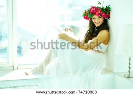 Beautiful woman in white dress posing before camera - stock photo
