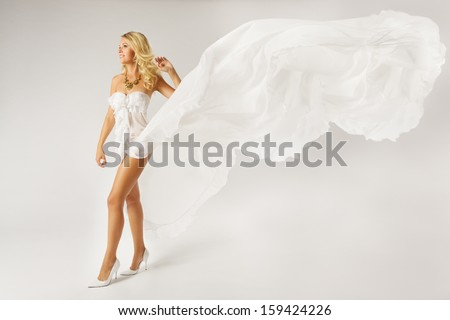 Beautiful woman in white dress with flying fabric walking   - stock photo
