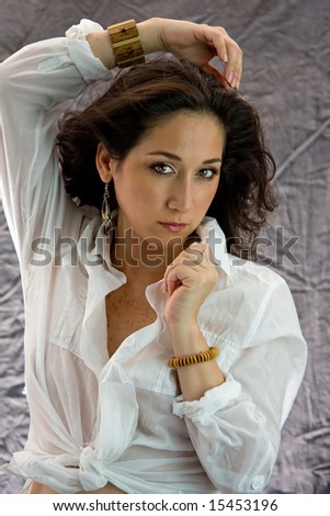 Beautiful woman in white shirt with a hand above her head and the other on the collar looking sensual - stock photo