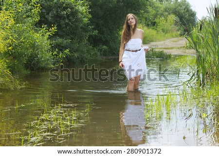 Beautiful woman in white summer dress walking at pool - stock photo