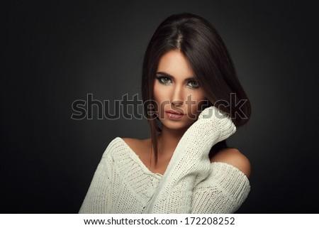 Beautiful woman in white sweater posing in studio on dark background - stock photo