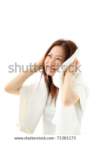 Beautiful woman in white vest wipes her wet hair with a towel - stock photo