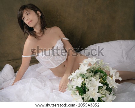 Beautiful Woman in White Vintage Lingerie With White Flowers on White Comforter