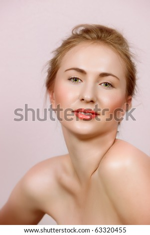 beautiful woman in with natural make-up on green eyes and coral lips on candy pink background. - stock photo