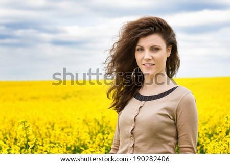 beautiful woman in yellow flower field - stock photo