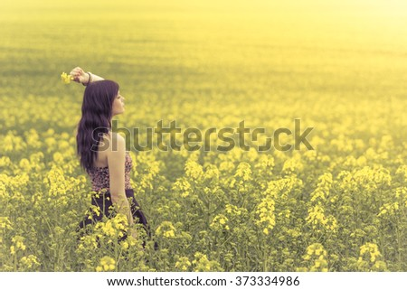 Beautiful woman in yellow flowers from side behind looking right. Attractive genuine young girl enjoying the warm summer sun in a wide green and yellow meadow. Part of series - stock photo