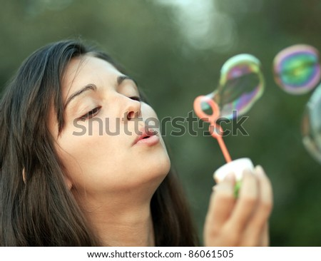 Beautiful woman inflating soap-bubbles