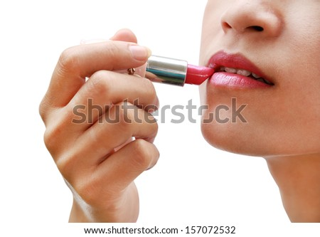 beautiful woman is applying her lips with pink lipstick on white background (with clipping path) - stock photo