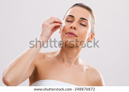 Beautiful woman is  cleaning  her face.Skin care - stock photo