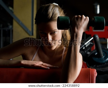 beautiful woman is doing exercises with dumbbells  in the sport club. - stock photo