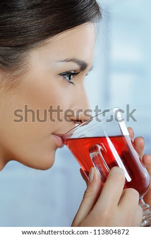 Beautiful woman is drinking healthy hot herbal tea - stock photo