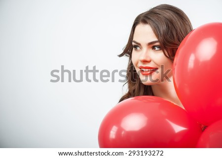 Beautiful woman is hiding behind red balloons and looking aside secretly. She is afraid of someone finding her. She is smiling. Isolated on grey background and there is copy space in the left side - stock photo