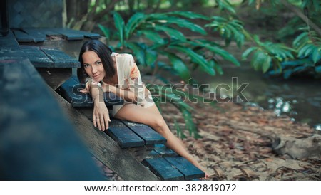 Beautiful woman is laying on the old wooden staircase on the tropical garden background. Focus point on the face. - stock photo