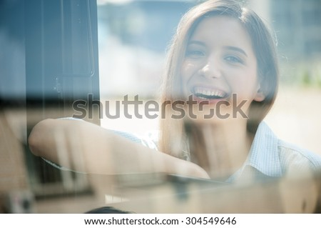 Beautiful woman is leaning on the handle of the bus and smiling. She is looking at the camera with joy - stock photo