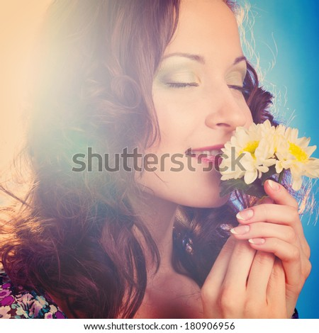 beautiful woman is pleasured with flower on blue background