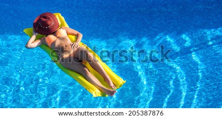 Beautiful woman is relaxing air mattress - stock photo