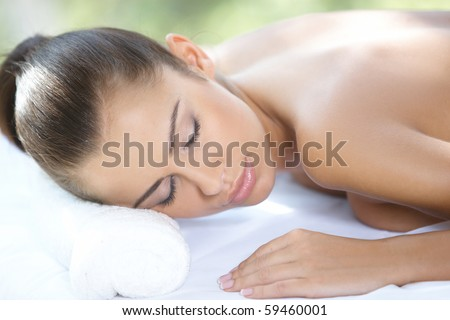 Beautiful woman is resting on spa bed - stock photo