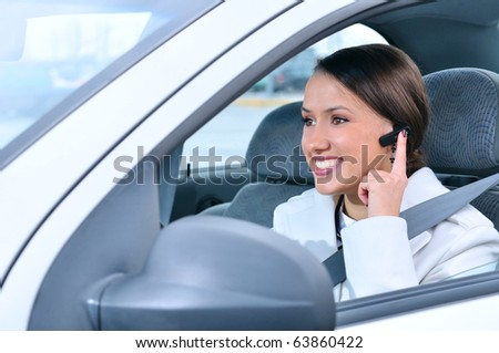 beautiful woman is safely talking phone in a car using a headset - stock photo