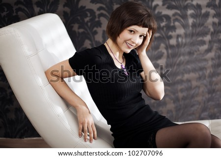 Beautiful woman is sitting on the couch - stock photo