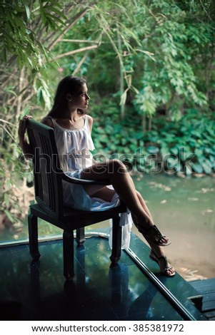 Beautiful woman is sitting on the old wooden chair on the tropical garden background. Portrait in the shadows. - stock photo