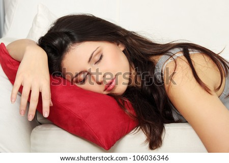 Beautiful woman is sleeping on red pillow. Pretty girl on the couch.
