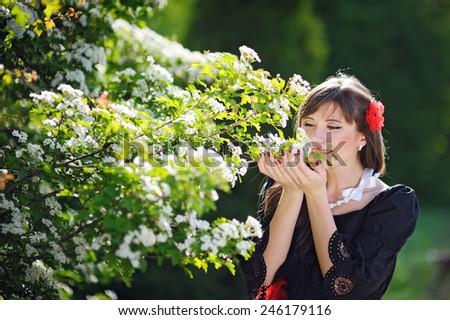beautiful woman is smelling white flowers in spring park. - stock photo