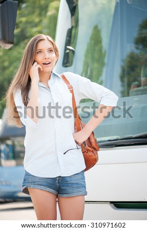 Beautiful woman is standing near a public transport. She is talking on the phone and expressing shock