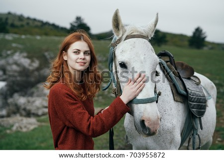 Beautiful woman is walking with a horse.