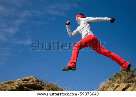 Beautiful woman jumping against blue sky - stock photo