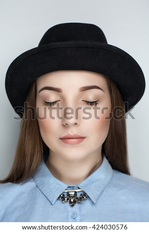Beautiful woman lady model wears fashionable black hat, formal blue blouse. Bright healthy long straight hair. beauty girl face professional makeup.