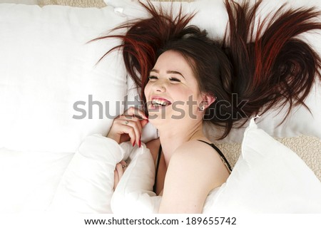Beautiful woman laid in bed laughing - stock photo