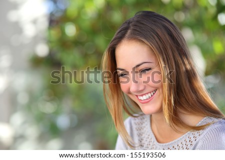 Beautiful woman laughing happy outdoor with a green unfocused background               - stock photo