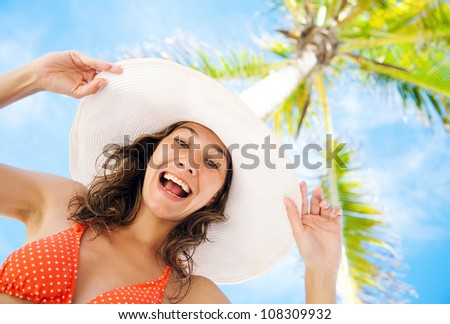 Beautiful woman laughing on the background of palm and blue sky - stock photo