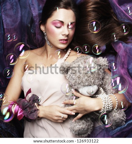 beautiful woman lay on organza with teddy bear - stock photo