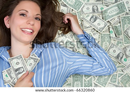 Beautiful woman laying in money - stock photo