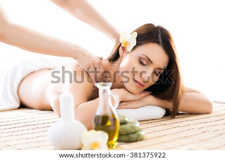 Beautiful woman laying on a mat having a smell of aroma in spa salon. - stock photo