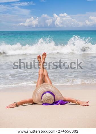 Beautiful woman laying on the beach in Jambara Bali Indonesia - stock photo